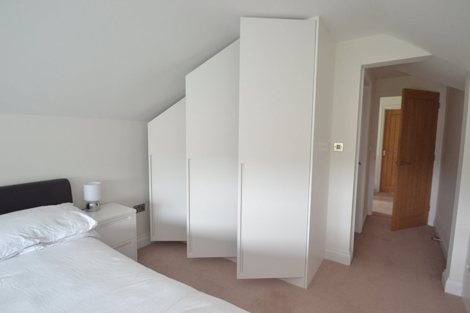Modern bedroom wardrobes fitted into angled ceiling